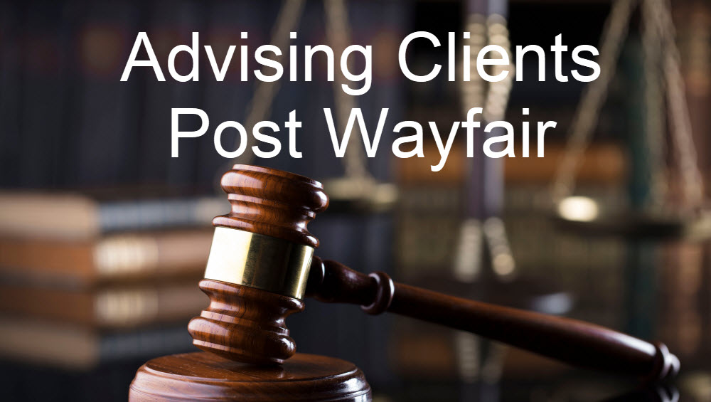 A brown glossy gavel with a gold band rests on a wooden pad. In the background there are books and a sclae. Text in the foreground reads 'Adivsing Clients Post Wayfair.'