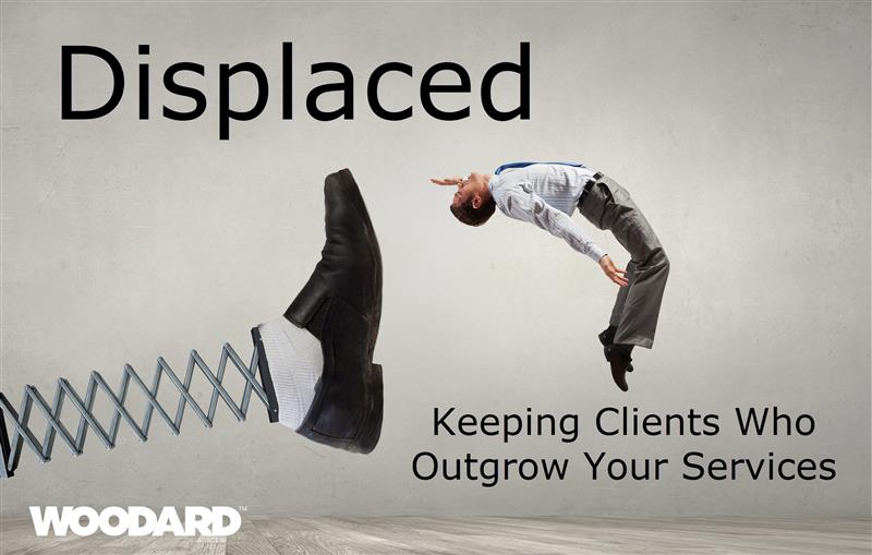 In large black font the word Displaced. Grey background and a large mechanical foot is kicking a man into the air. White woodard logo in the upper right hand corner and text in the bottom right hand corner reads - keeping clients who outgrow your services.